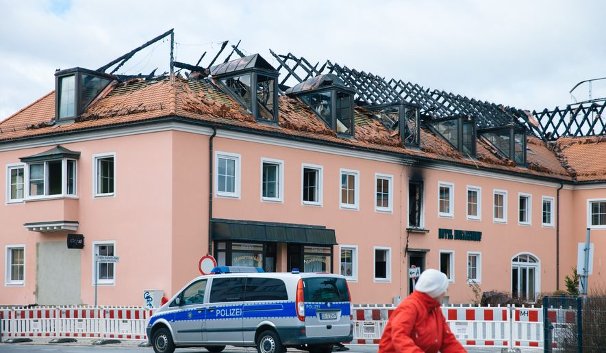 A police car stands in front of  a building with burned down roof  in Bautzen, eastern Germany,  Monday Feb. 22, 2016.  A fire damaged the former hotel that was being converted into a refugee home and two people were detained after hindering firefighters' work, police said days after an incident in which a mob blocked a bus carrying asylum-seekers in the same state.  (Oliver Killig/dpa via AP)