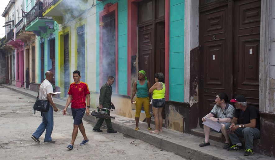 A soldier carrying a fumigating machine enters a home as residents wait outside in Havana, Cuba, Monday, Feb. 22, 2016. Cuban President Raul Castro announced Monday that he is dispatching soldiers to help keep the Zika virus out of Cuba, calling on the entire country to help kill the mosquito that carries the disease. Castro says Cuba has yet to report a case of Zika. (AP Photo/Desmond Boylan)