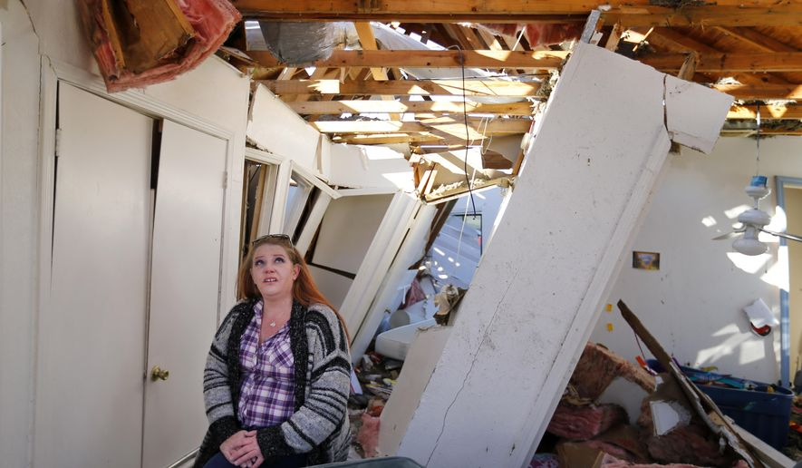 In this Friday, Jan. 22, 2016 photo, homeowner Amanda Bose talks about how her house came apart in her tornado devastated home in Rowlett, Texas. She and her family found safety in the bathroom as the walls of her Fox and Jacobs home collapsed around them. Experts are looking at building standards following late-December tornadoes that slammed parts of North Texas. (Tom Fox/The Dallas Morning News via AP) MANDATORY CREDIT