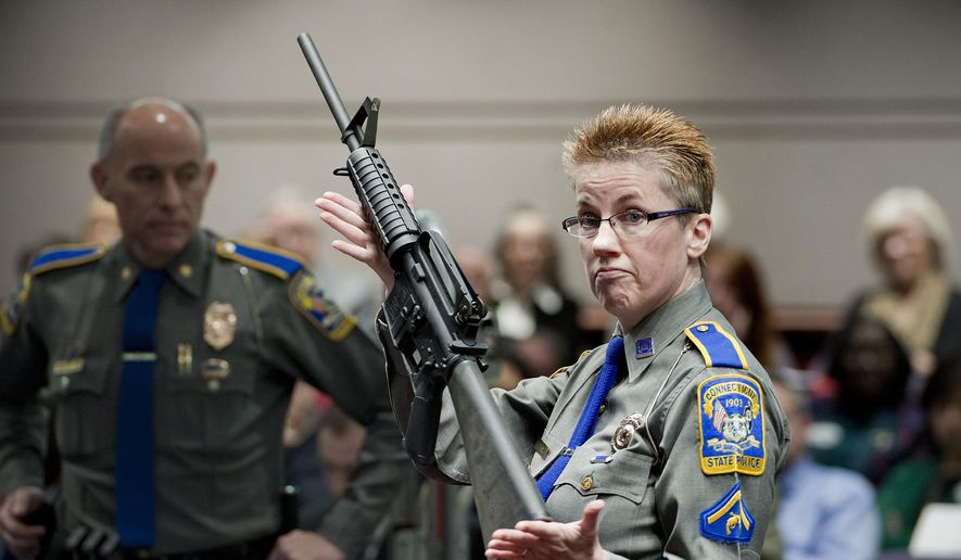 In this Jan. 28, 2013, file photo, firearms training unit Detective Barbara J. Mattson, of the Connecticut State Police, holds up a Bushmaster AR-15 rifle, the same make and model of gun used by Adam Lanza in the Sandy Hook School shooting, during a hearing of a legislative subcommittee, at the Legislative Office Building in Hartford, Conn. (AP Photo/Jessica Hill, File)