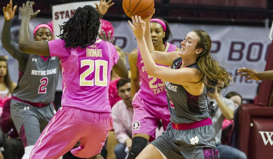 Notre Dame guard Marina Mabrey, right, passes the ball against Florida State forwards Shakayla Thomas (20) and Ivey Slaughter (23) in the first half of an NCAA college basketball game in Tallahassee, Fla., Monday, Feb. 22, 2016. (AP Photo/Mark Wallheiser)