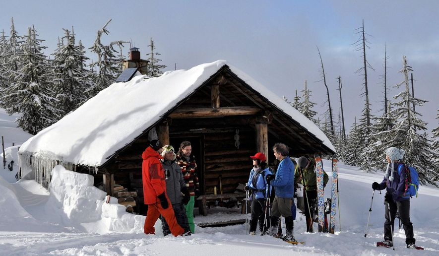 In this Jan. 30, 2016, photo, backcountry skiers and boarders staying at the Snow Peak Cabin greet group of snowshoers out for a day hike in the Sherman Pass area of the Colville National Forest in Washington. (Rich Landers/The Spokesman-Review via AP) COEUR D'ALENE PRESS OUT; MANDATORY CREDIT