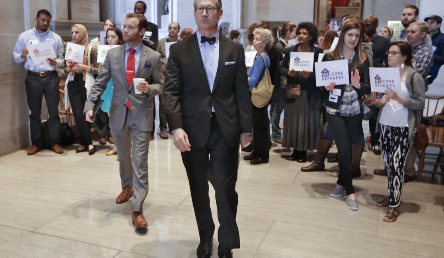 Sen. Bo Watson, center, R-Hixson, walks past demonstrators opposed to immigration restrictions outside the Senate Chamber on Monday, Feb. 22, 2016, in Nashville, Tenn. The state Senate has passed a resolution on a 27-5 vote directing Tennessee's attorney general to mount a legal challenge to the federal refugee resettlement program. (AP Photo/Mark Humphrey)