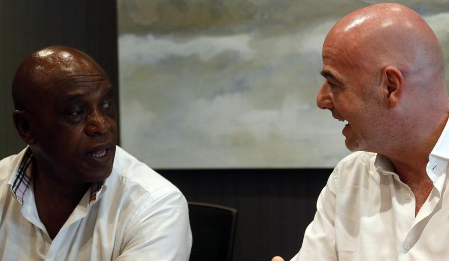 Gianni Infantino UEFA secretary general, right, speaks to fellow FIFA candidate South African Tokyo Sexwale, at a press briefing in Cape Town, South Africa, Monday, Feb. 22, 2016.  Infantino expects more than half of Africa's 54 countries to back him in the FIFA presidential election on Friday. (AP Photo/Schalk van Zuydam)