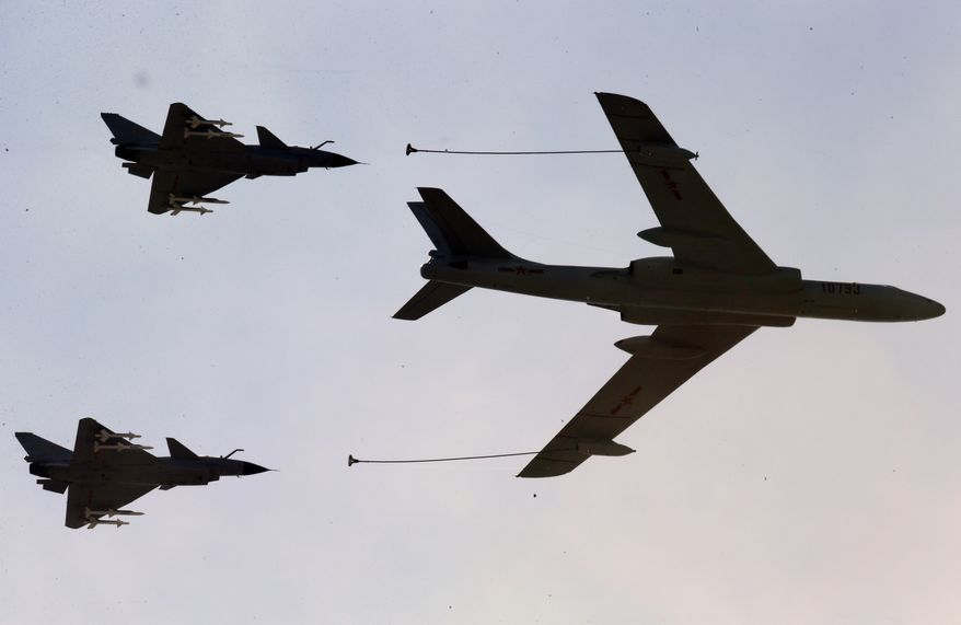 A Chinese military refueling tanker flies with fighter jets during a parade commemorating the 70th anniversary of Japan's surrender during World War II held in front of Tiananmen Gate in Beijing on Sept. 3, 2015. (Associated Press) ** FILE **