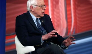 Democratic presidential candidate, Sen. Bernie Sanders, I-Vt., talks with host Chris Cuomo during commercial break in a CNN town hall style televised event at the University of South Carolina School of Law, in Columbia, S.C., Tuesday, Feb. 23, 2016. (AP Photo/Gerald Herbert)