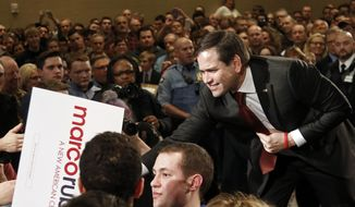 Republican presidential candidate, Sen. Marco Rubio, R-Fla., reaches into the crowd to shake hands at a campaign rally Tuesday, Feb. 23, 2016, in Minneapolis.  (AP Photo/Jim Mone)