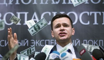 Russian opposition activist Ilya Yashin speaks while fake banknotes thrown at him by protesters, as Yashin presents a report on Chechen leader Ramzan Kadyrov, in Moscow, Tuesday, Feb. 23, 2016.  The report from Yashin accuses Chechen leader Kadyrov of corruption, while the protesters accuse Yashin of working for Western interests and throw symbolic fake money at him. (AP Photo/Alexander Zemlianichenko )