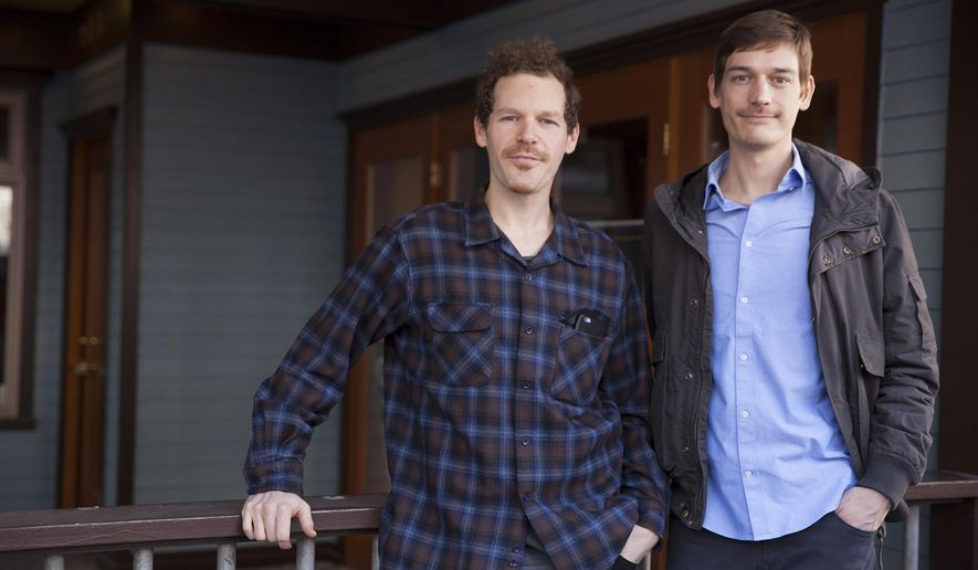 Giono Barrett, left, and James Barrett stand outside of the shop that will be a downtown retail storefront for their marijuana business, Rainforest Farms, Tuesday, Feb. 23, 2016, in Juneau, Alaska. A state board tasked with regulating Alaska's nascent legal pot industry will begin taking business license applications Wednesday, setting the stage for legal sales set to occur later this year.  (AP Photo/Rashah McChesney)