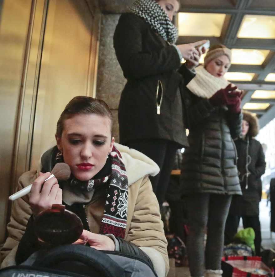 """Courtney Tierchoski, 25, from Nashville, Tenn., applies makeup while on line with other dancers outside Radio City Music Hall waiting to audition for """"Rockettes New York Spectacular"""" on Tuesday, Feb. 23, 2016, in New York.  Tierchoski said she hope the third is the charm as she hopes to land a spot in the summertime production from June 15 through Aug. 7, 2016.  (AP Photo/Bebeto Matthews)"""