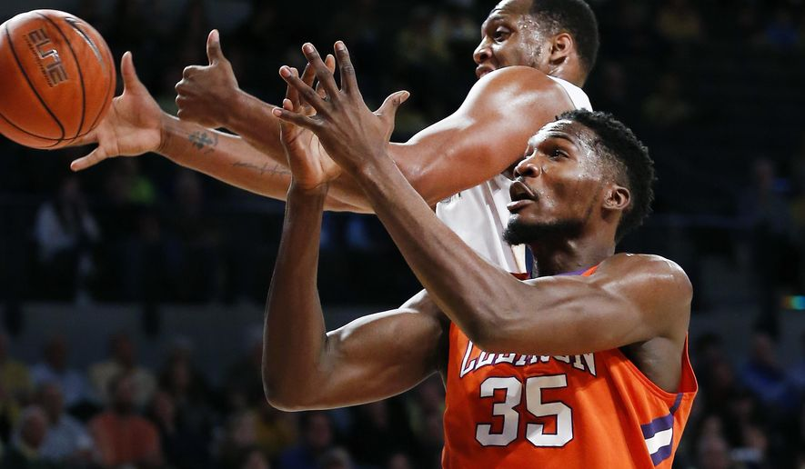 Georgia Tech forward Charles Mitchell (0) and Clemson center Landry Nnoko (35) vie for a rebound during the first half of an NCAA college basketball game Tuesday, Feb. 23, 2016, in Atlanta.  (AP Photo/John Bazemore)