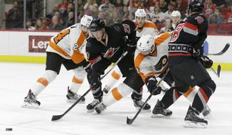Carolina Hurricanes'  Riley Nash (20) and Jay McClement (18) struggle with Philadelphia Flyers' Radko Gudas (3), of the Czech Republic, and Matt Read (24) during the second period of an NHL hockey game in Raleigh, N.C., Tuesday, Feb. 23, 2016. (AP Photo/Gerry Broome)
