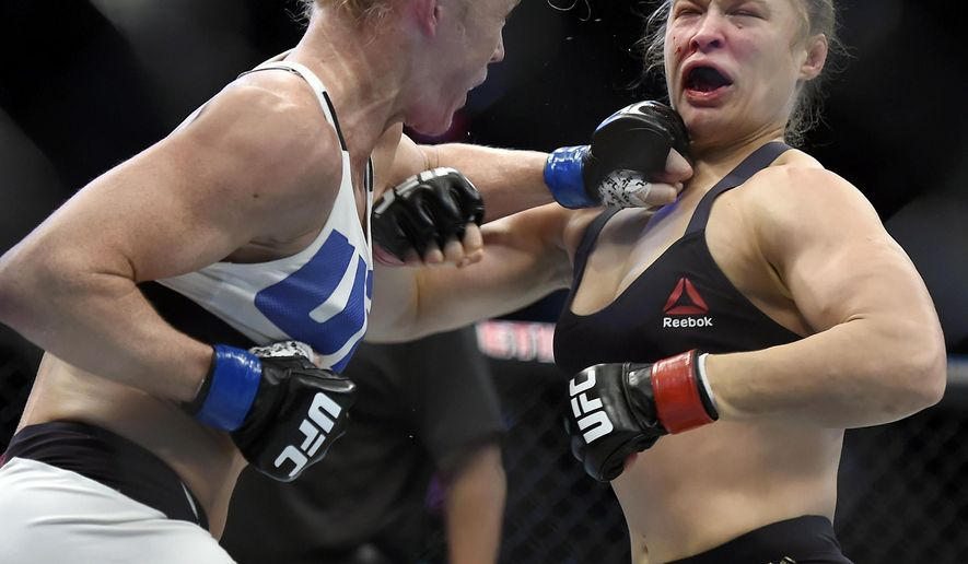 FILE - In this Nov. 15, 2015, file photo, Holly Holm, left, punches Ronda Rousey during their UFC 193 bantamweight mixed martial arts title fight in Melbourne, Australia. Holm felt compassion after learning Rousey had suicidal thoughts following their bout last year and is fairly certain Rousey wouldn't want her sympathy, the UFC bantamweight champion said in a recent television interview. (AP Photo/Andy Brownbill, File)