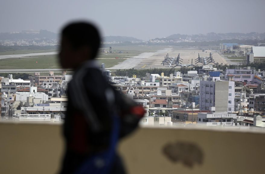 FILE - In this March 23, 2015, file photo, a child looks at the U.S. Marine Corps Futenma Air Station and the surrounding area from an observation deck at a park in Ginowan, Okinawa Prefecture on southern Japan. U.S. Adm. Harry Harris told a congressional committee in Washington on Tuesday, Feb. 23, 2016 that the shift of the Futenma air station to the town of Henoko would not happen until 2025 because construction has slowed. (AP Photo/Eugene Hoshiko, File)