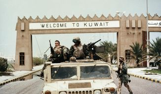 "In this Wednesday, Feb. 27, 1991, file photo, members of Task Force Ripper of the First Marine Division ride a Humvee under a ""Welcome to Kuwait"" sign at the entrance to Kuwait City's International Airport. In February 1991, after months of building an international coalition, U.S. forces entered Kuwait to end the Iraqi occupation of its smaller, oil-rich neighbor. (AP Photo/Patrick Downs, File)"