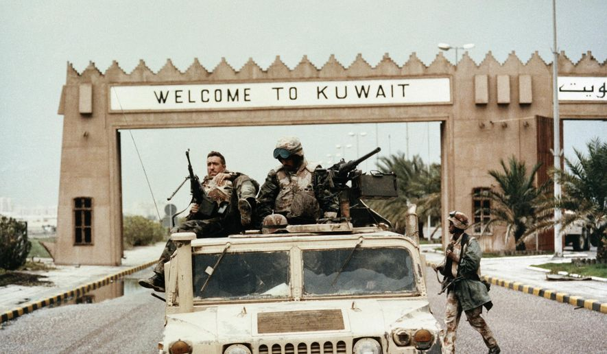 """In this Wednesday, Feb. 27, 1991, file photo, members of Task Force Ripper of the First Marine Division ride a Humvee under a """"Welcome to Kuwait"""" sign at the entrance to Kuwait City's International Airport. In February 1991, after months of building an international coalition, U.S. forces entered Kuwait to end the Iraqi occupation of its smaller, oil-rich neighbor. (AP Photo/Patrick Downs, File)"""