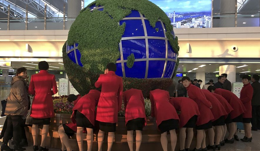 North Korea's women soccer team fills up custom forms in front of a globe structure as they prepare for departure from Pyongyang to Beijing on Tuesday, Feb. 23, 2016, at Pyongyang's International Airport in Pyongyang, North Korea. (AP Photo/Wong Maye-E)