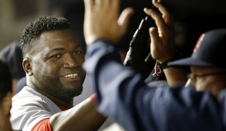 FILE - In this Sept. 29, 2015, file photo, Boston Red Sox's David Ortiz, left, is greeted by teammates in the dugout after scoring on Brock Holt's double in the first inning of a baseball game against the New York Yankees in New York. Ortiz hopes his 20th and final big league season will be up to the standard he has set for himself. Big Papi announced in November on his 40th birthday that he planned to retire after 2016. (AP Photo/Kathy Willens, File)