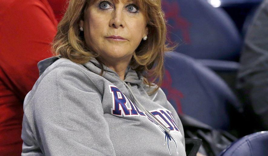 """This Saturday Feb. 13, 2016, photo shows Hall of Famer Nancy Lieberman, mother of University of Richmond's T.J. Cline, with her puppy, """"Magic"""" prior to the start of a basketball game against Fordham at the Robins Center in Richmond Va. Lieberman sees some of herself in her son's unselfish tendencies. (Mark Gormus/Richmond Times-Dispatch via AP)"""