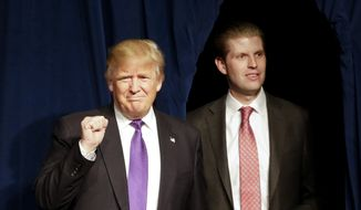 Republican presidential candidate Donald Trump, left, arrives with his son Eric during a caucus night rally Tuesday, Feb. 23, 2016, in Las Vegas. (AP Photo/Jae C. Hong)