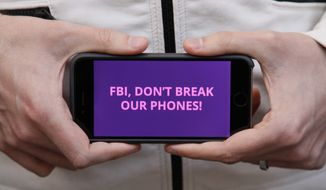 A man holds out his iPhone during a rally in support of data privacy outside the Apple store Tuesday, Feb. 23, 2016, in San Francisco. Protesters assembled in more than 30 cities to lash out at the FBI for obtaining a court order that requires Apple to make it easier to unlock an encrypted iPhone used by a gunman in December's mass murders in California. (AP Photo/Eric Risberg)