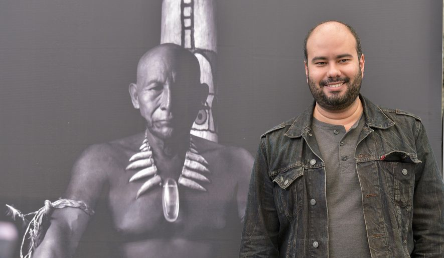 """FILE - In this Jan. 14, 2016 file photo, Colombian director Ciro Guerra, a first-time Oscar finalist, stands in front of a movie poster featuring Antonio Bolivar Salvador as old Karamakate during promotion of his film, """"Embrace of the Serpent,"""" at a press conference in Bogota, Colombia,  """"Embrace of the Serpent"""" is among five nominees competing for the best foreign-language film at the 88th Academy Awards to be presented Feb. 28, 2016 in Los Angeles. Shot in black and white the movie tells the story of the relationship between an Amazonian shaman and two scientists who work together to search the Amazon for a sacred healing plant. (AP Photo/Santiago Cortez, File)"""