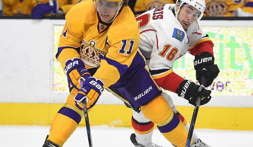 Los Angeles Kings center Anze Kopitar, left, of Slovenia, and Calgary Flames center Josh Jooris vie for the puck during the first period of an NHL hockey game Tuesday, Feb. 23, 2016, in  Los Angeles. (AP Photo/Mark J. Terrill)