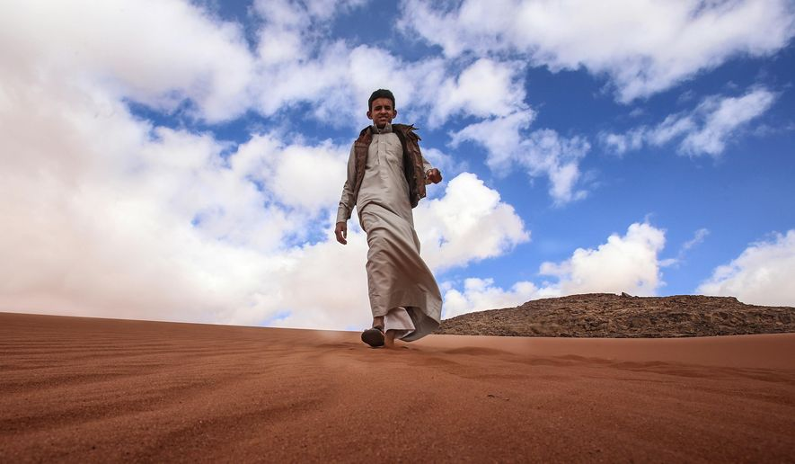 """FILE - In this Saturday, Jan. 9, 2016 file photo, Jacir Eid Al-Hwietat, 15, poses for a photo in Wadi Rum, a scenic desert area of southern Jordan. Jacir and his cousin, both from a Bedouin clan, acted in the film """"Theeb"""" (Wolf), a coming-of-age drama set in 1916, that has emerged as the first Oscar contender of Jordan's nascent film industry. (AP Photo/Raad Adayleh, File)"""