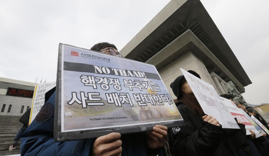 """South Korean protesters shout slogans during a rally to oppose the possible deployment of the United States' advanced defense system THAAD, or Terminal High-Altitude Area Defense, on Korea Peninsula,  in Seoul, South Korea, Thursday, Feb. 25, 2016. The United States and China have reached agreement on a U.N. resolution that would impose tougher sanctions on North Korea as punishment for its latest nuclear test and rocket launch, U.N. diplomats said Wednesday. The signs read """" Oppose  deployment of the THAAD."""" (AP Photo/Ahn Young-joon)"""