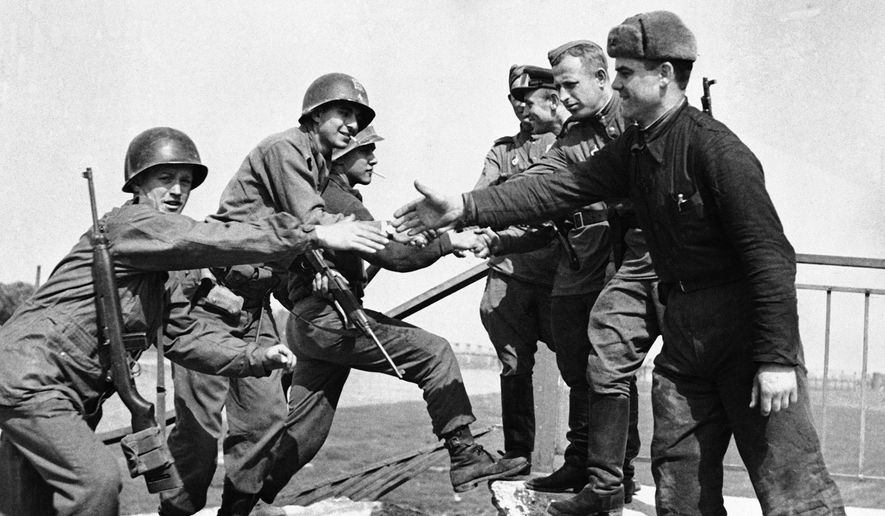 U.S. and Russian troops meet on the wrecked bridge over the Elbe River at Torgau, Germany, April 26, 1945. The Americans, left, and Russian soldiers are shown as they reach out to grasp each other's hands. (AP Photo)