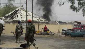Nigerian soldiers patrol outside the site of an accidental explosion in Yola, Nigeria, Thursday, Feb. 25, 2016. Bombs retrieved from Boko Haram exploded accidentally Thursday at police headquarters in Nigeria's northeastern city of Yola, killing four people and wounding a score of officers and school children cut by shattered glass, officials said. (AP Photo) ** FILE **