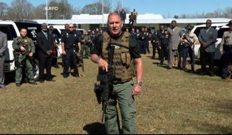 "Capt. Clay Higgins of the Acadiana Sheriff's Office in Louisiana stands in front of community members and law enforcement in a video urging the community to help capture members of the violent ""Gremlins gang."" (Image: KATC)"