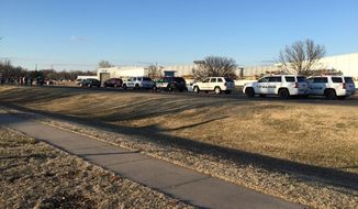 Police vehicles line the road after a reported shooting at Excel Industries in Hesston, Kansas, on Thursday. (KWCH-TV via Associated Press)
