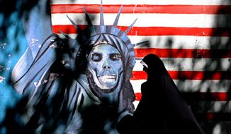 In this Tuesday, Sept. 25, 2007, file photo, a veiled Iranian woman walks past graffiti art characterizing the U.S. Statue of Liberty, painted on the wall of the former U.S. Embassy in Tehran, Iran. (AP Photo/Vahid Salemi, FIle)