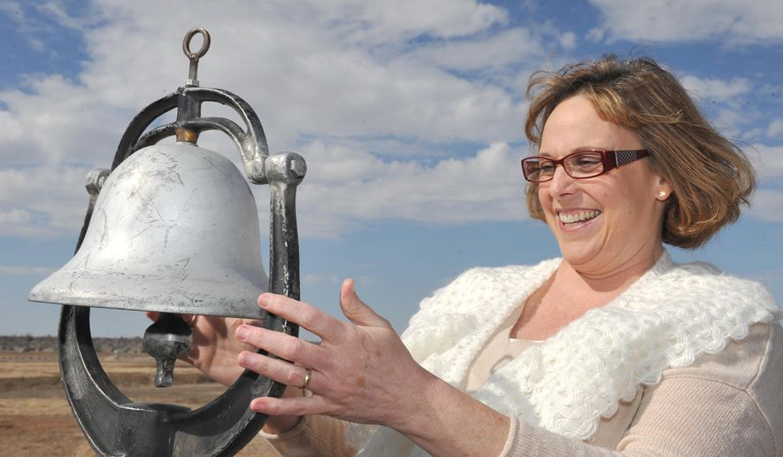 In this Feb. 22, 2016, photo, Barbara Logan poses for a photo with a train bell in Amarillo, Texas, that she remembers ringing in the 1980s when she worked on the Sad Monkey in Palo Duro Canyon. Logan is restoring the old train with the help of Randall County Sheriff's crews and will place the train on display in a City of Canyon Park. (Michael Schumacher/The Amarillo Globe News via AP) MANDATORY CREDIT