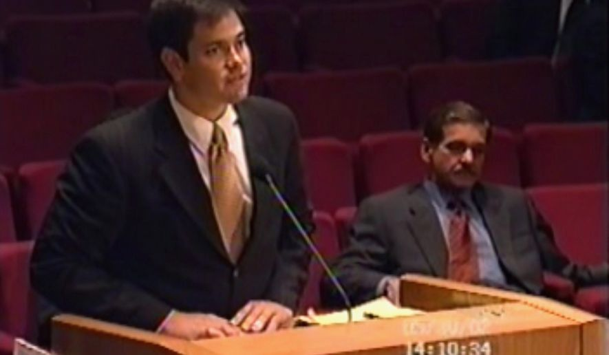 This frame grab made from standard definition video from a Miami-Dade County Commission meeting on May 30, 2002, shows Marco Rubio, left, pushing for approval of a development project backed by Carlos C. Lopez-Cantera, seated at right. Rubio was in the Florida House Republican leadership at the time. Years before his Republican presidential bid, Rubio pushed Miami-Dade County officials to allow a major industrial development to be built on restricted land near the Florida Everglades. That was two months after he backed a law as a member of the Florida Legislature that made it harder for people to challenge the kinds of developments he advocated for as a private attorney. (Miami-Dade Board of County Commissioners via AP)