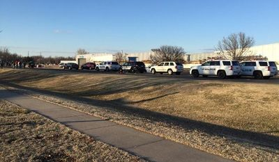 Police vehicles line the road after a shooting at Excel Industries in Hesston, Kansas, on Thursday. (KWCH-TV via Associated Press)