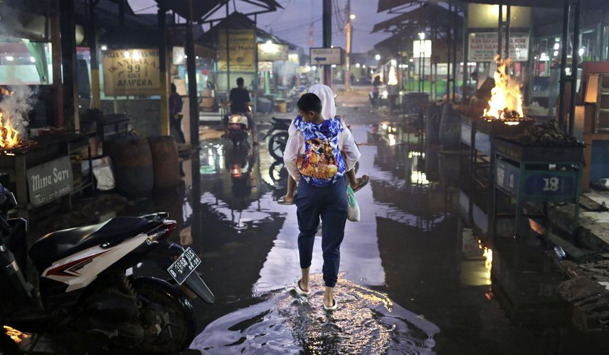 A woman carries a boy through a flooded alley following a heavy rain in Jakarta, Indonesia, Friday, Feb. 26, 2016. (AP Photo/Dita Alangkara) ** FILE **