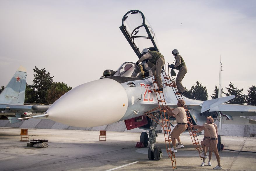 FILE - In this file photo taken on Thursday, Oct.  22, 2015, Russian air force pilots assisted by ground crew climb into their fighter jet at Hemeimeem airbase, Syria. (AP Photo/Vladimir Isachenkov, File)