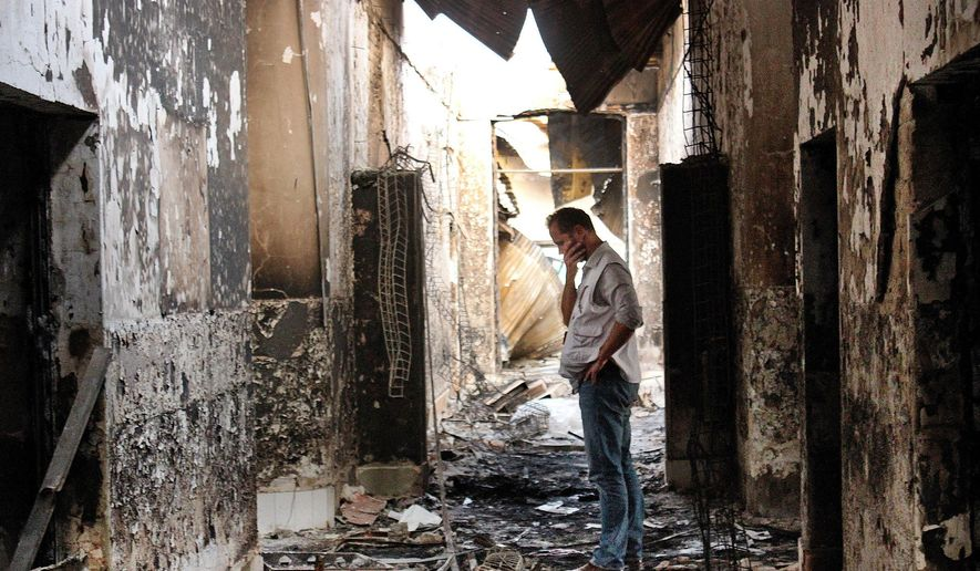 """In this Friday, Oct. 16, 2015, file photo, an employee of Doctors Without Borders walks inside the charred remains of the organization's hospital after it was hit by a U.S. airstrike in Kunduz, Afghanistan. The U.S. military is paying hundreds of thousands of dollars to wounded survivors and relatives of the 42 Afghans killed when an American AC-130 gunship attacked the hospital; Doctors Without Borders says the """"sorry money"""" doesn't compensate for the loss of life. (AP Photo/Najim Rahim, File)"""