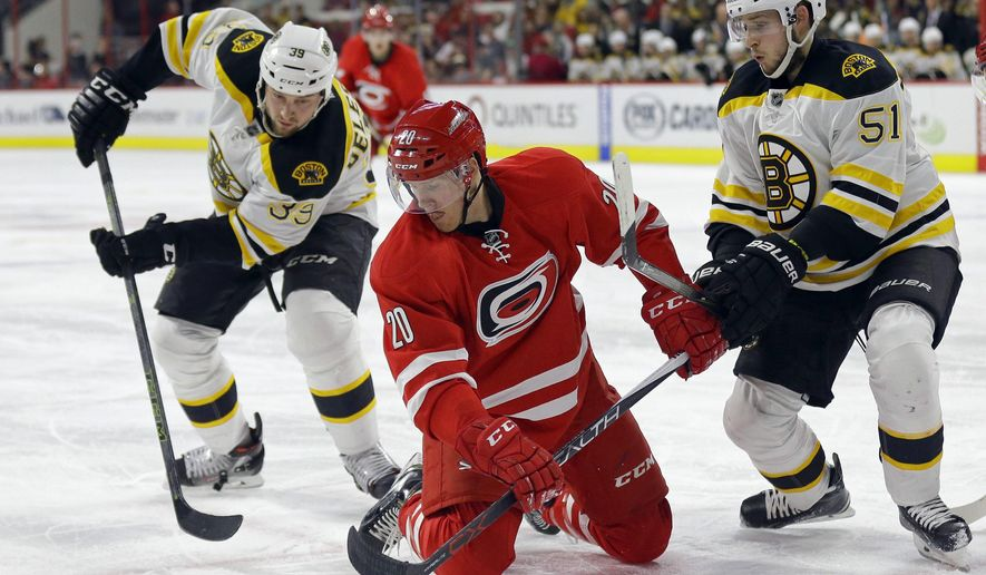 Boston Bruins' Matt Beleskey (39) and Ryan Spooner (51) struggle with Carolina Hurricanes' Riley Nash (20) during the second period of an NHL hockey game in Raleigh, N.C., Friday, Feb. 26, 2016. (AP Photo/Gerry Broome)