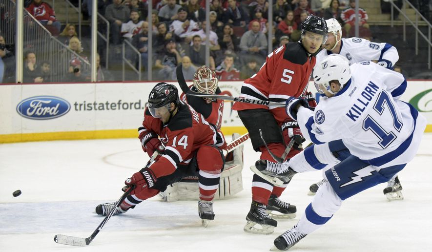 Tampa Bay Lightning's Alex Killorn (17) scores a goal past New Jersey Devils' Adam Henrique (14), goaltender Cory Schneider, and Adam Larsson (5) during the first period of an NHL hockey game Friday, Feb. 26, 2016, in Newark, N.J. (AP Photo/Bill Kostroun)