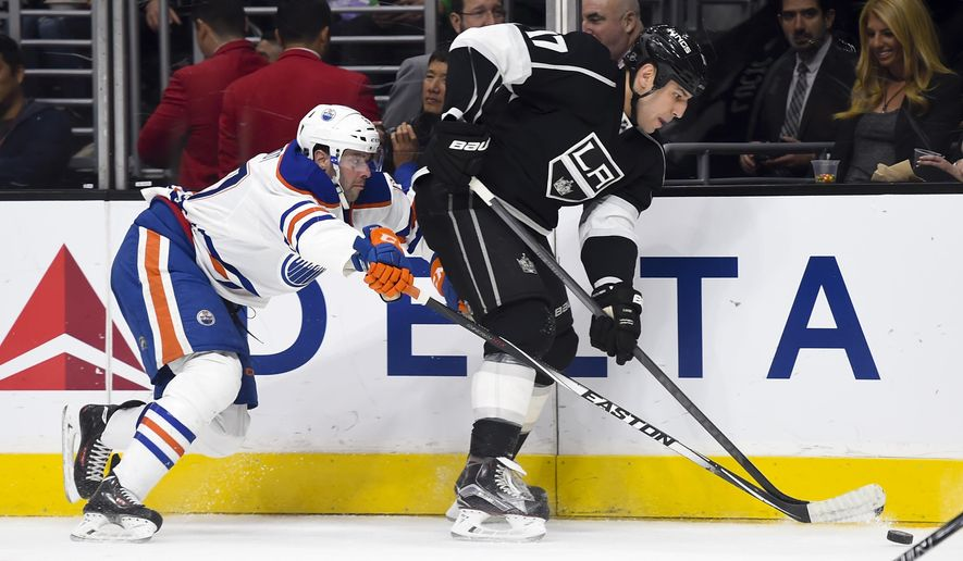 Edmonton Oilers left wing Benoit Pouliot, left, and Los Angeles Kings left wing Milan Lucic (17) vie for the puck during the first period of an NHL hockey game, Thursday, Feb. 25, 2016, in Los Angeles. (AP Photo/Gus Ruelas)