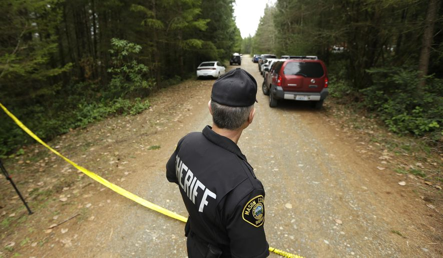 Mason County Sheriff's Chief Criminal Deputy Russ Osterhout looks down a road near the scene of a fatal shooting Friday, Feb. 26, 2016, near Belfair, Wash. (AP Photo/Ted S. Warren)