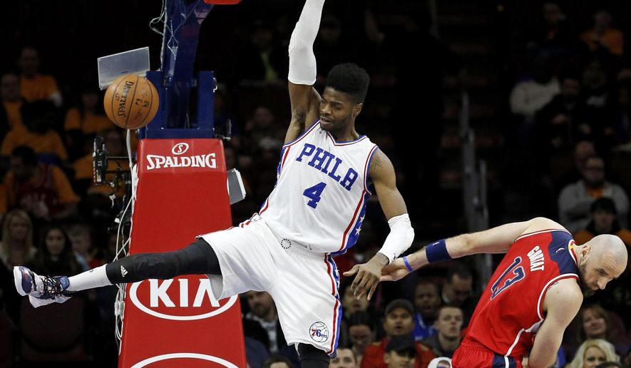 Philadelphia 76ers' Nerlens Noel, left, dunks past Washington Wizards' Marcin Gortat during the first half of an NBA basketball game Friday, Feb. 26, 2016, in Philadelphia. (AP Photo/Matt Slocum)