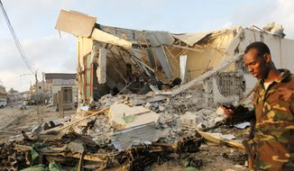 A Somali soldier walks near destroyed buildings, Saturday, Feb. 27, 2016, after a suicide car bomb on Friday night in Mogadishu, Somalia. (AP Photo/Farah Abdi Warsameh) ** FILE **