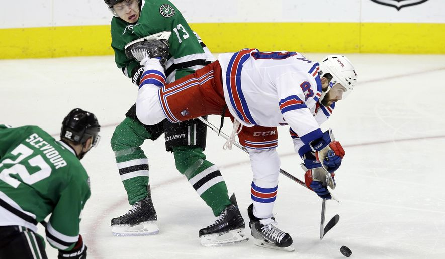 New York Rangers defenseman Keith Yandle (93) reaches for the puck against Dallas Stars center Mattias Janmark (13) as Stars' Colton Sceviour (22) looks on during the third period of an NHL hockey game Saturday, Feb. 27, 2016, in Dallas. The Rangers won 3-2. (AP Photo/LM Otero)