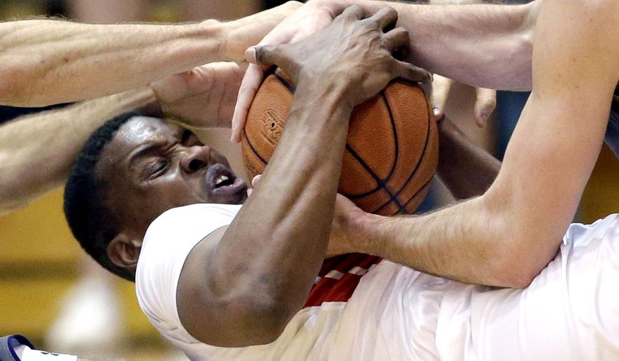 Rutgers forward/center Ibrahima Diallo battles for a loose ball against  Northwestern guard Tre Demps, left, and guard Bryant McIntosh during the second half of an NCAA college basketball game Saturday, Feb. 27, 2016, in Evanston, Ill. Northwestern won 98-59. (AP Photo/Nam Y. Huh)