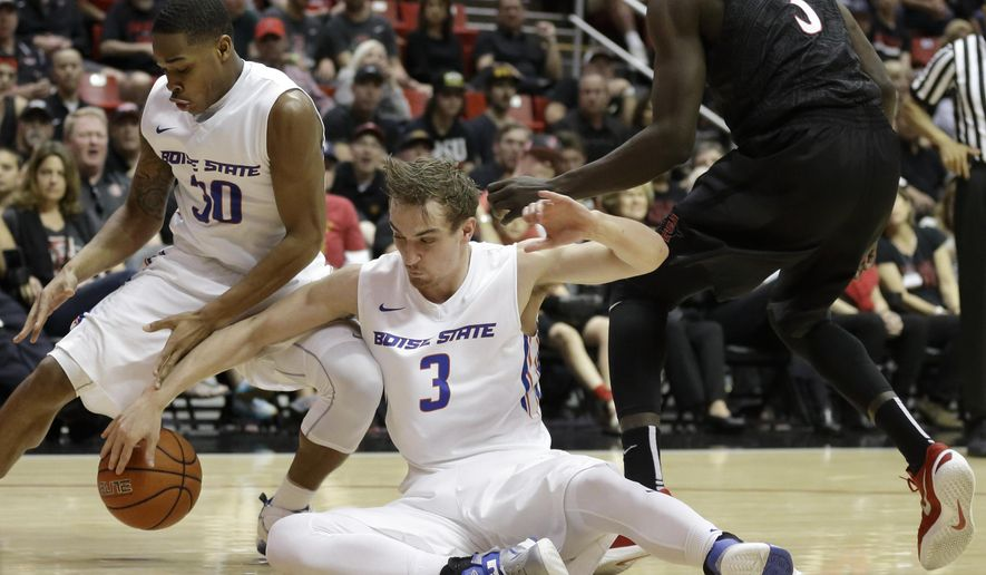 Boise State guard Anthony Drmic (3) and teammate guard Paris Austin (30) grab for the ball during the first half of an NCAA college basketball game against San Diego State, Saturday, Feb. 27, 2016, in San Diego. (AP Photo/Gregory Bull)