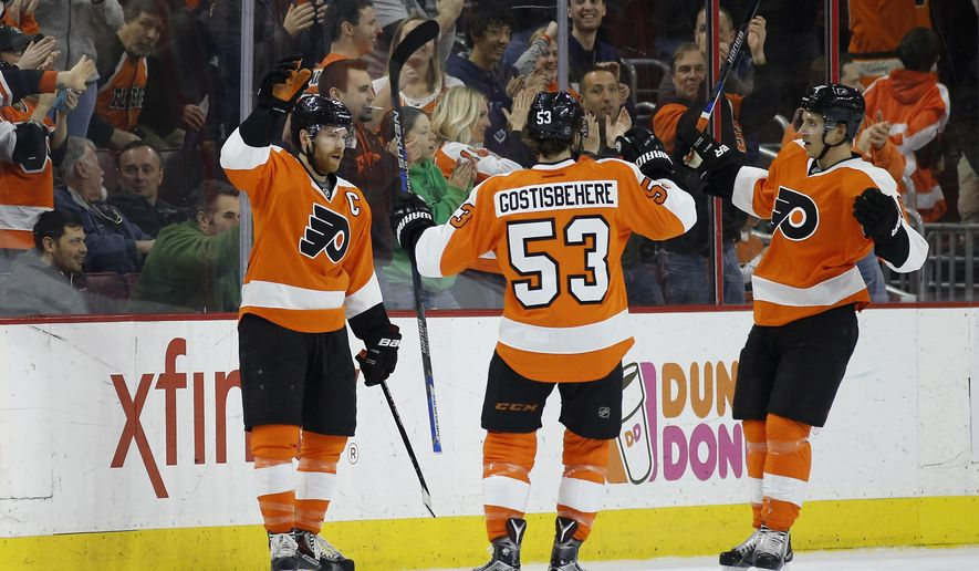 Philadelphia Flyers' Claude Giroux, left, Shayne Gostisbehere and Brayden Schenn celebrate after Giroux's goal during the first period of an NHL hockey game against the Arizona Coyotes, Saturday, Feb. 27, 2016, in Philadelphia. Philadelphia won 4-2. (AP Photo/Matt Slocum)